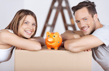 A man and a woman with a  piggy bank smiling.