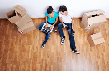 a couple sitting on the floor with a laptop and coffee between boxes