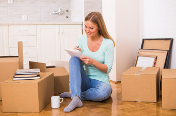 A woman writing something while surrounded by boxes