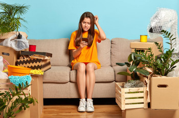 Confused girl sitting on a couch surrounded by belongings, scrolling on her phone