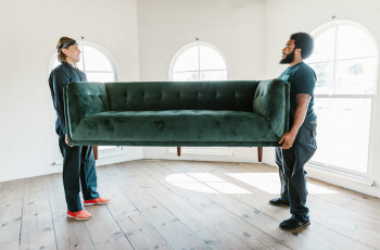 Long-distance movers in denim carrying a couch