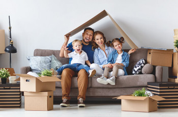 Family on the couch, smiling, surrounded by moving boxes