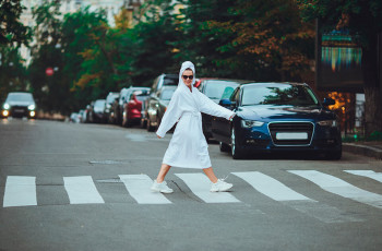 A woman crossing a street in her bathrobe