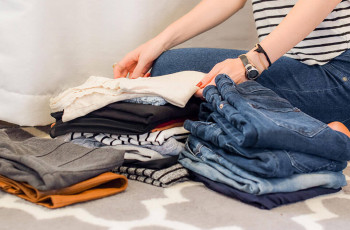 Person organizing jeans and shirts