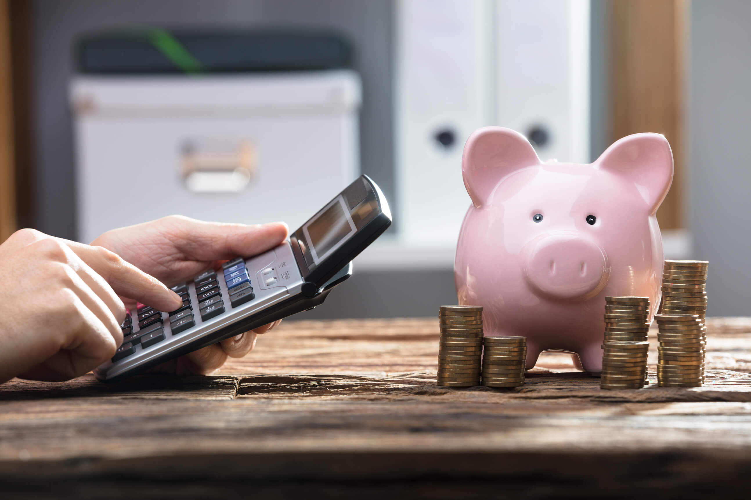 a person using a calculator and a pink piggy bank