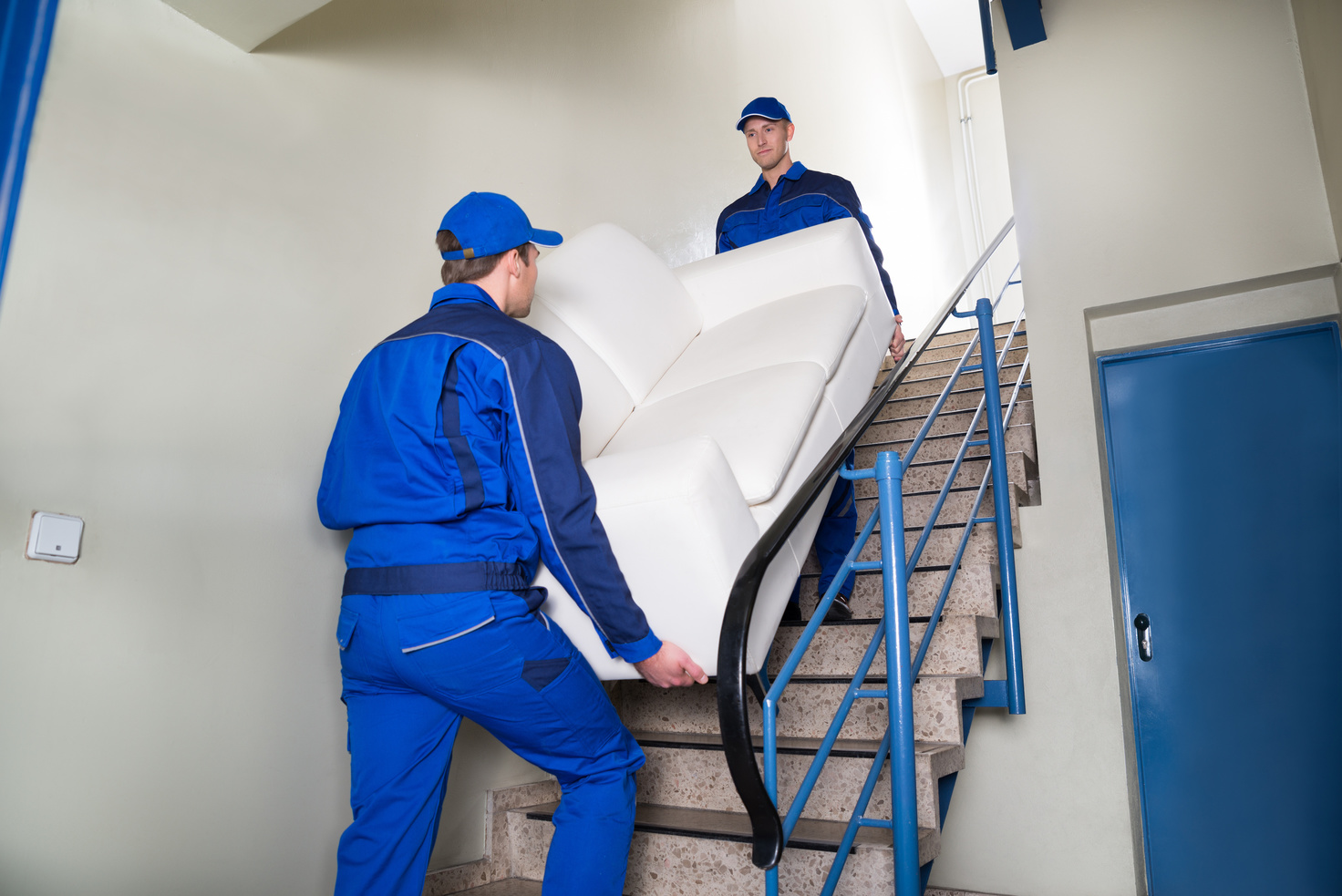 relocation specialists taking a sofa upstairs