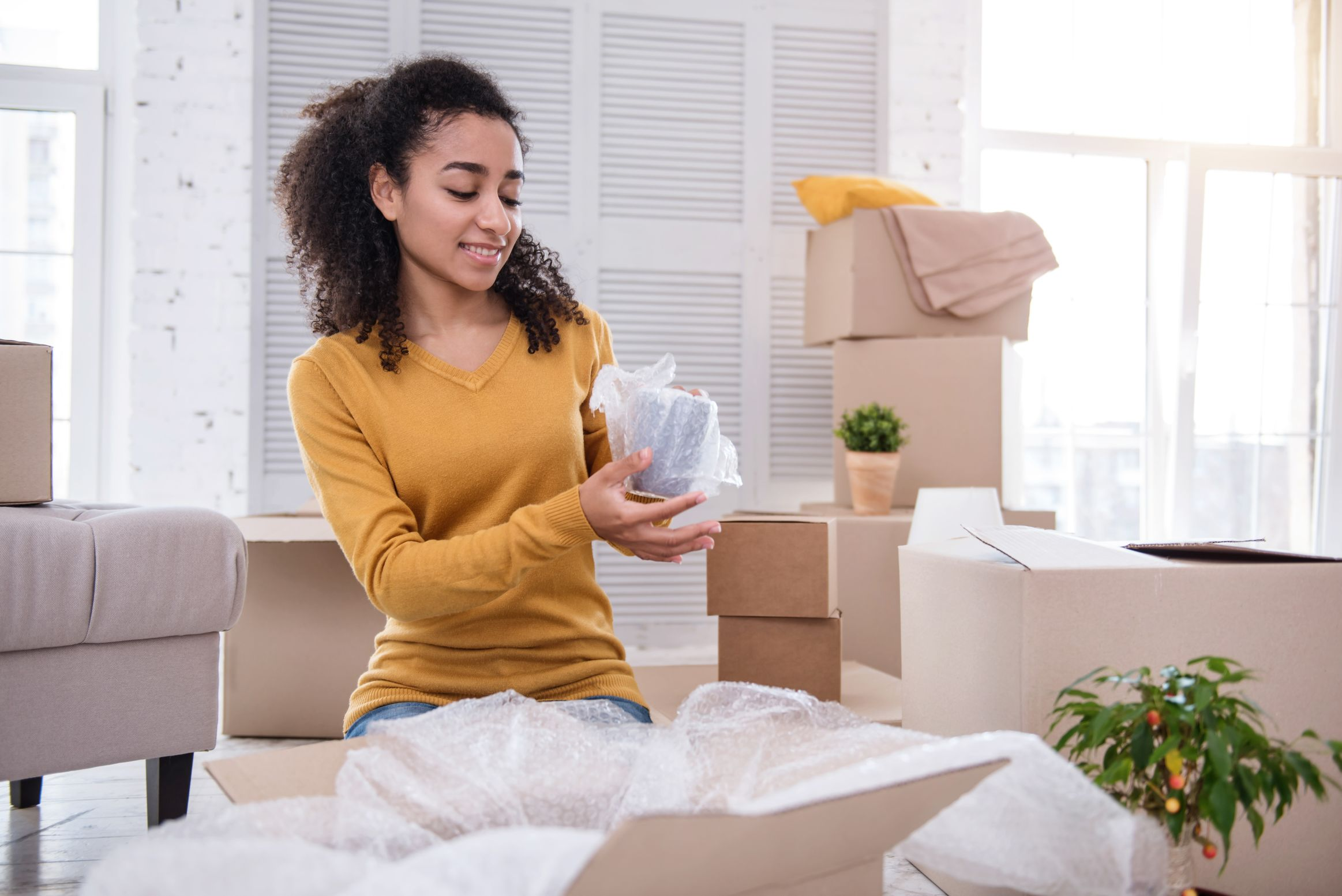 A girl at home wrapping up a cup in a bubble wrap without any help from movers
