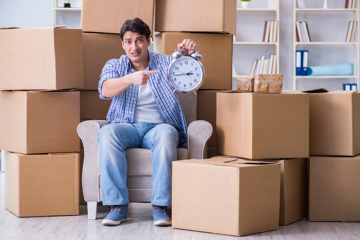 A stressed-out man sitting among new boxes pointing at a clock