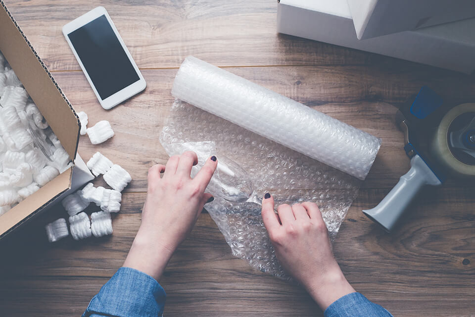 Woman packing a piece of stemware with bubble wrap
