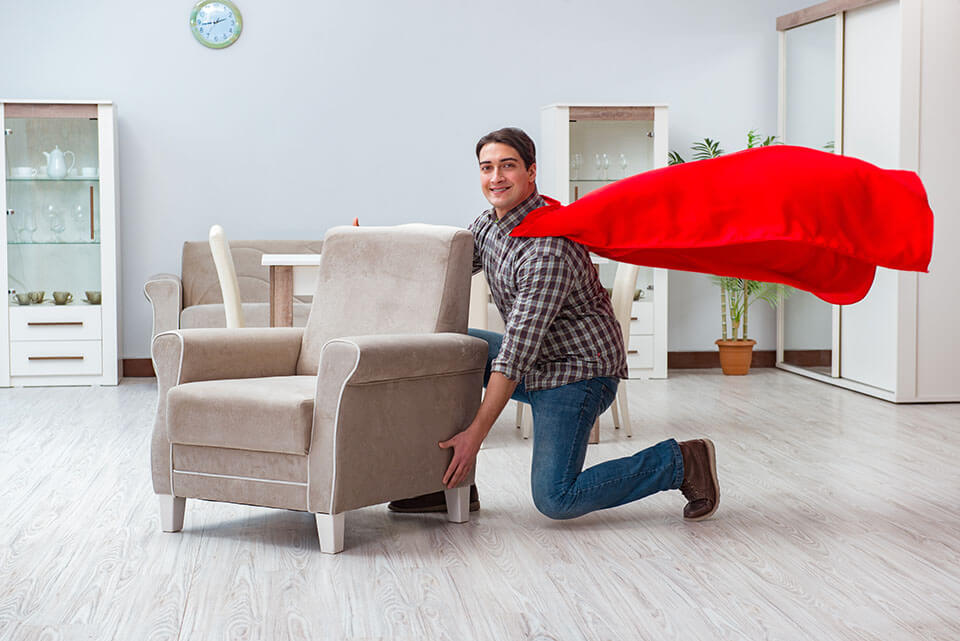 A man with a cape about to lift an armchair