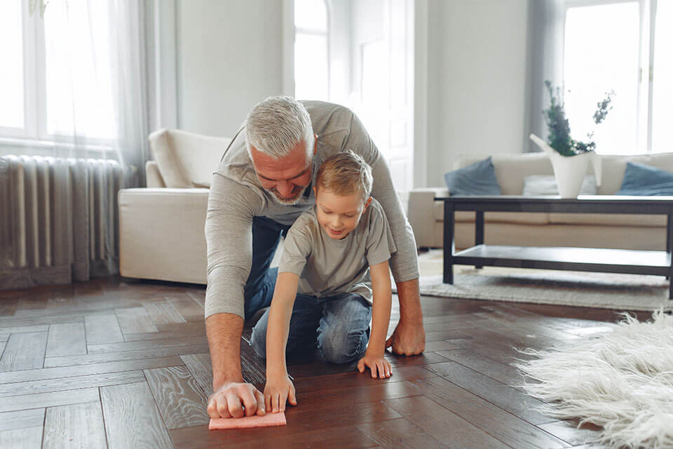 A boy and an older man cleaning a floor