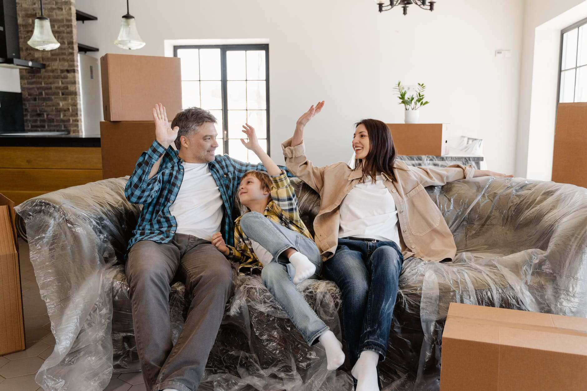 a family in the living room sitting on a sofa, enjoying their place after the moving company delivered their belongings
