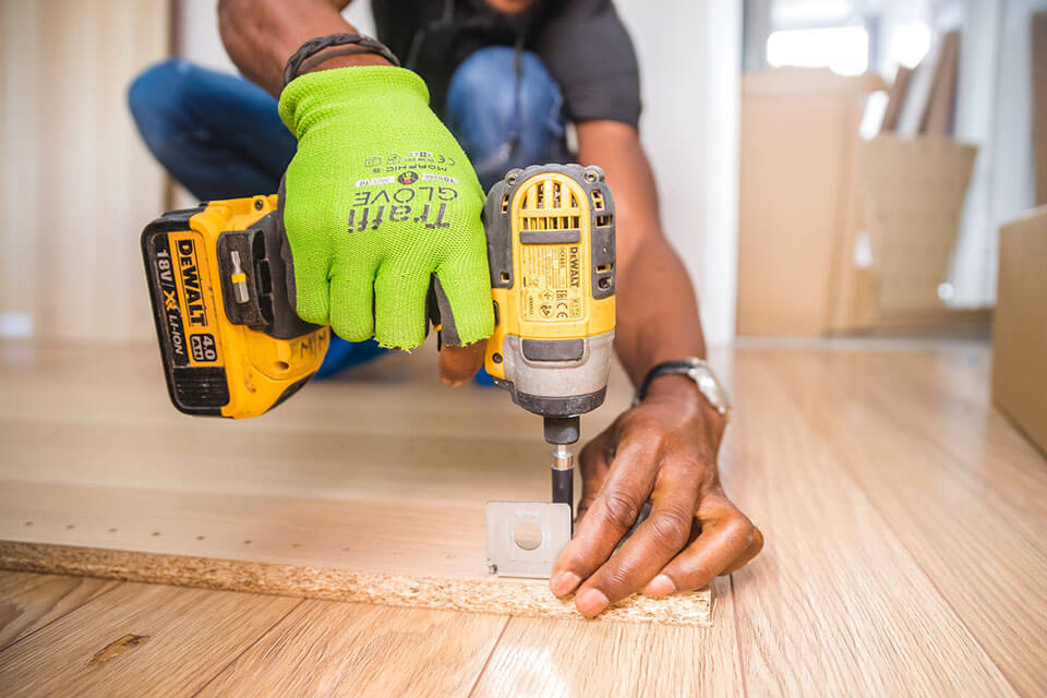 a man unscrewing table legs and preparing furnishings for a moving company
