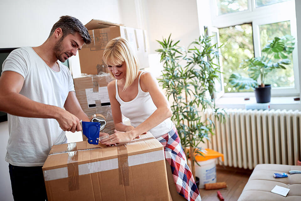 two friends packing their stuff after finding a moving company on a moving app