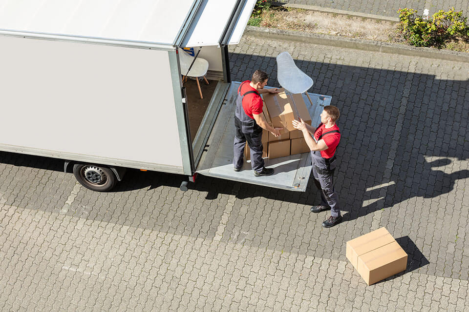 two movers packing chairs and containers into the relocation truck