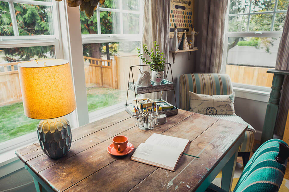 an old wooden table placed in front of a window that overlooks a backyard