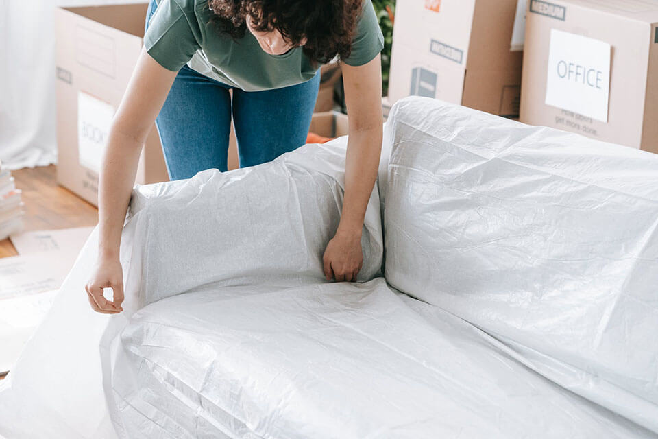 a woman in a green t-shirt packing her couch and preparing for a moving company