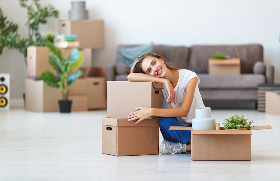 Girl sitting on the floor, leaning on packages, and smiling after hiring a moving company