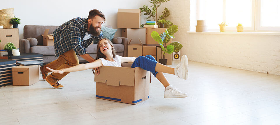 Man pushing a package with a girl sitting in it, after finding movers via an app to compare moving companies