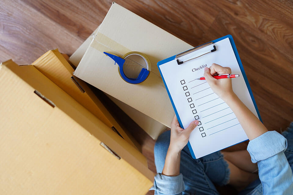 Person holding a pen and a checklist, standing next to packages