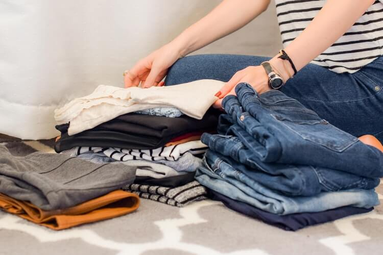 A woman deciding which clothes to keep after using a moving company app