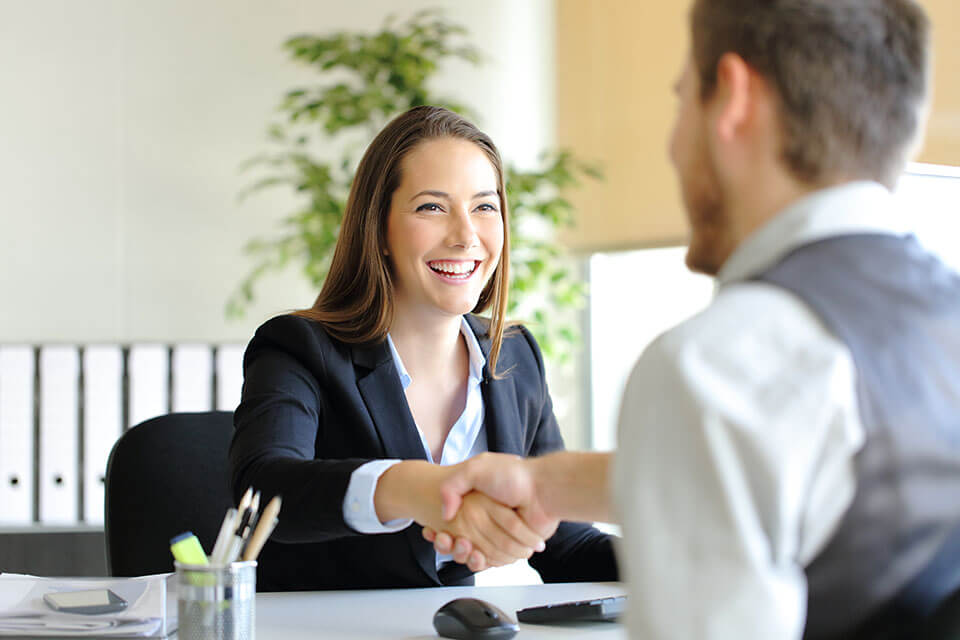 A customer and a moving company representative shaking hands