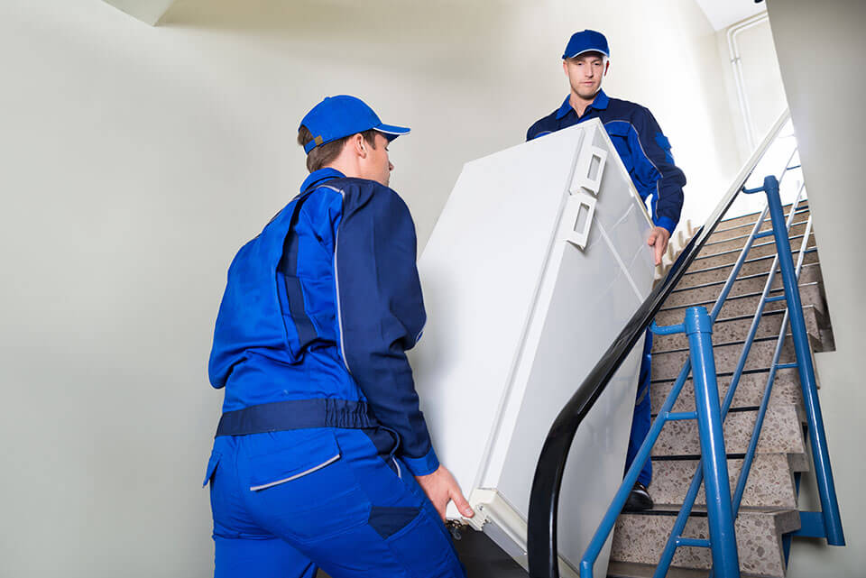 Moving company professionals carrying a refrigerator