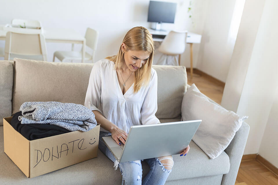 A woman with a laptop and a donation box ready for a moving company