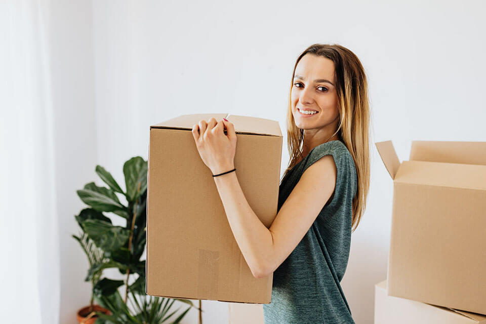 A girl holding a box and smiling after finding a moving app