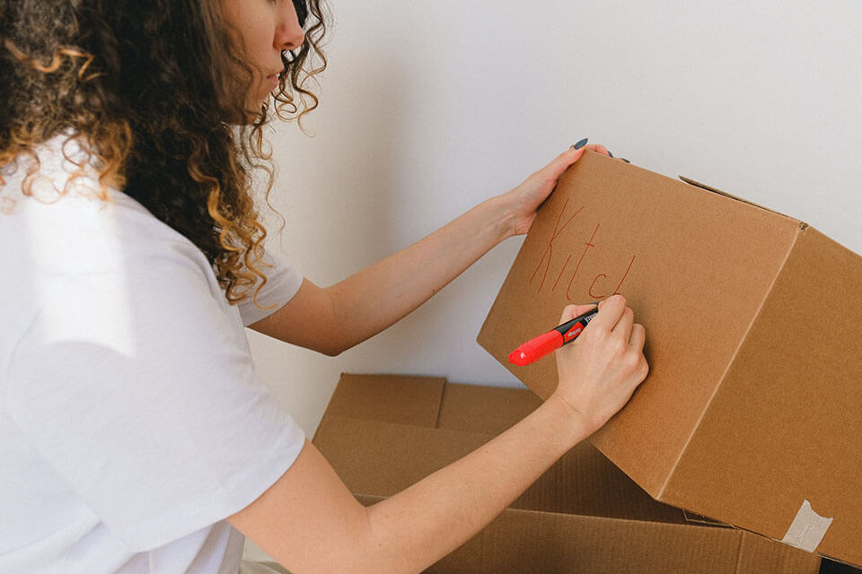A woman labeling a box after using a moving app to find a moving company