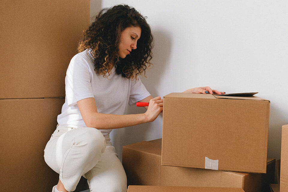 A woman writing labels on the boxes after she found an app to compare moving companies