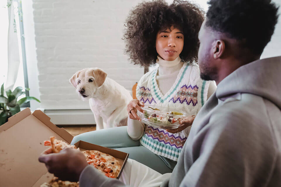 a young couple and their dog eating dinner together