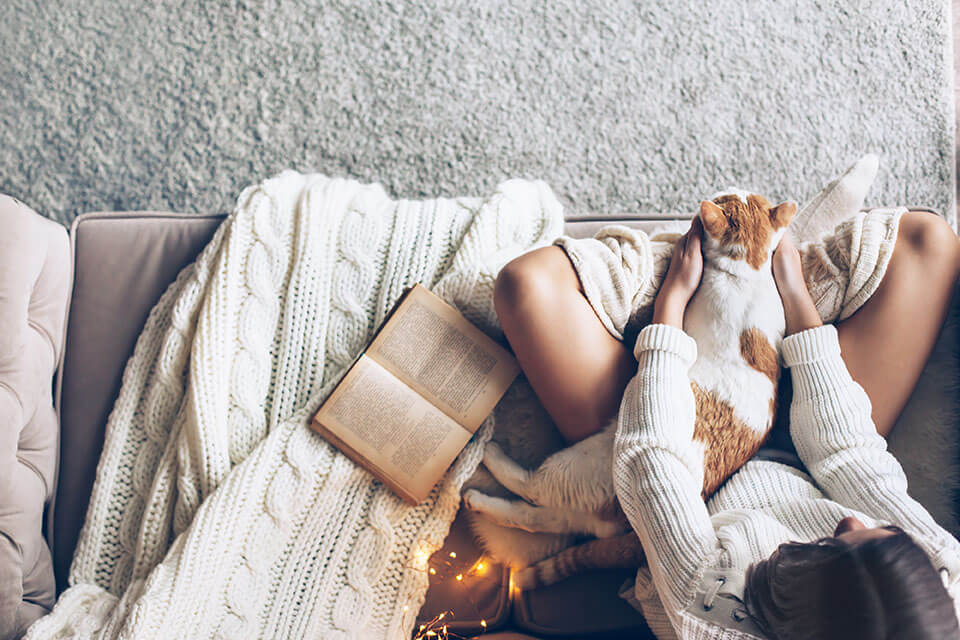 A girl and a cat reading a book together