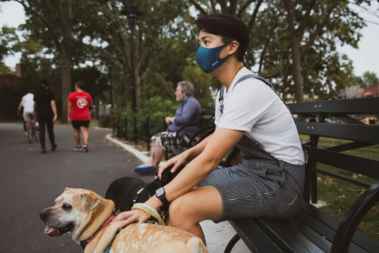 A man with a mask sitting on the bench in the park, his canine companion next to him