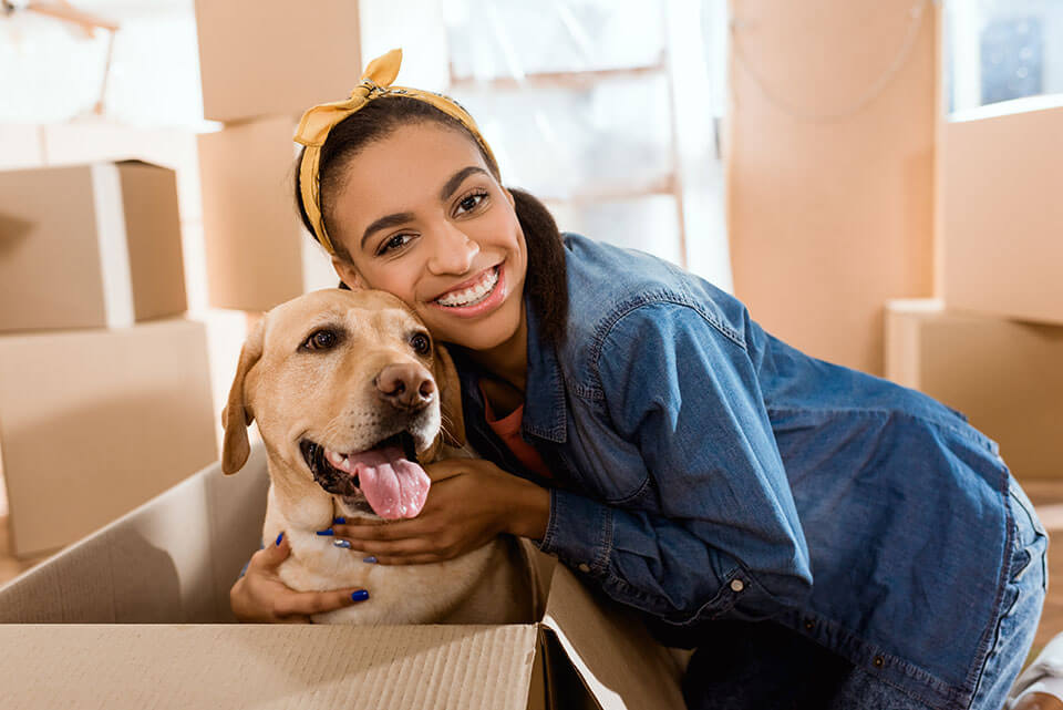A smiling girl hugging a golden retriever in the box, packages behind them