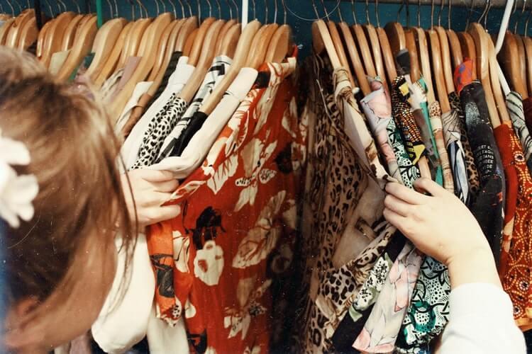 Girl going through shirts on a clothing rack