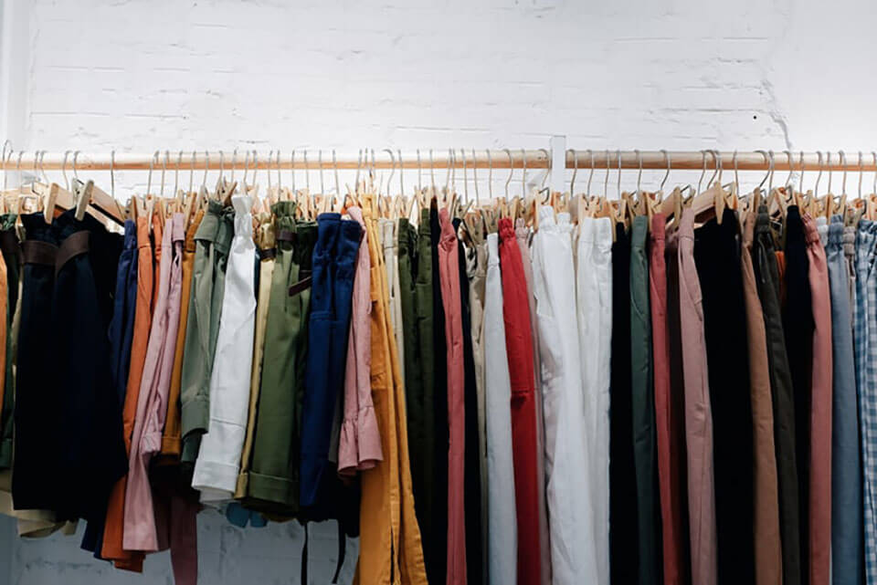 Jeans and shirts hanging on a rack