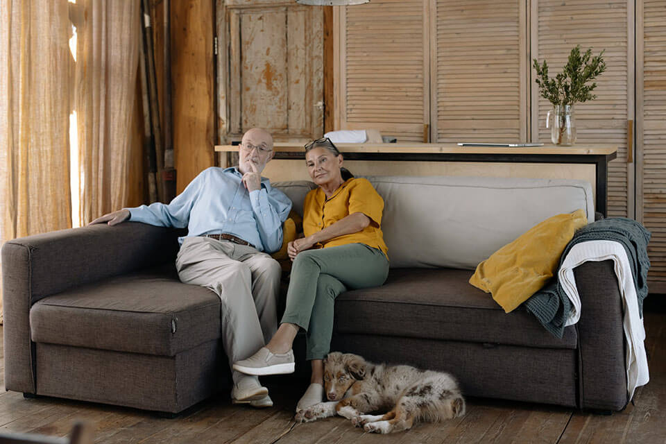 An older couple sitting on a sofa