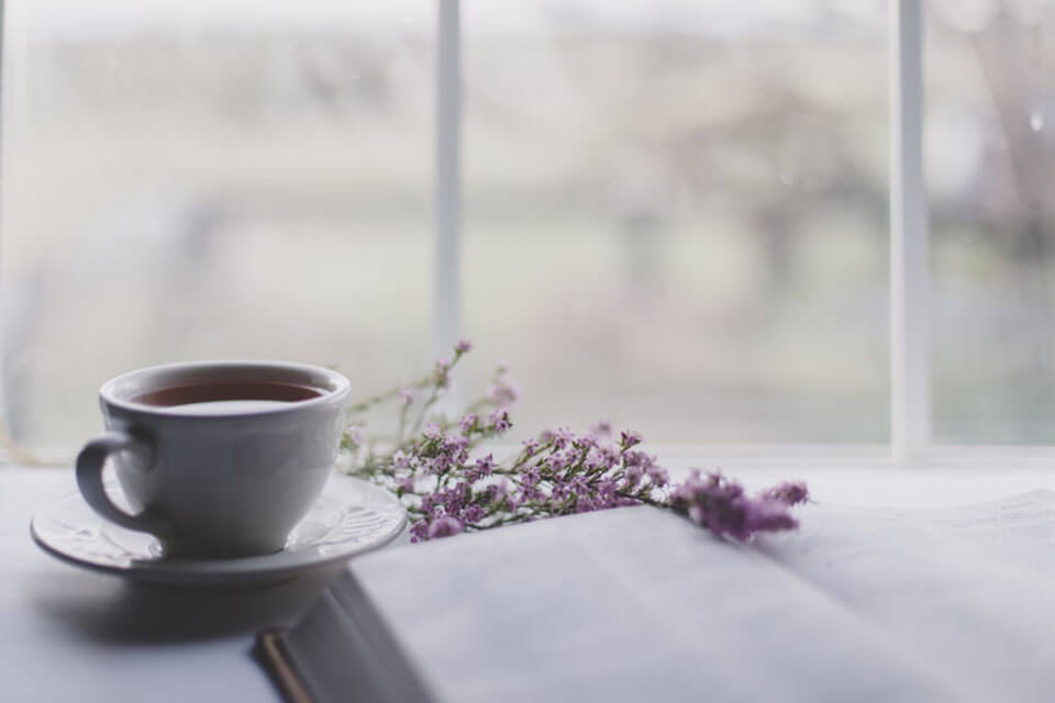 A cup of tea, book, and flowers on the white surface