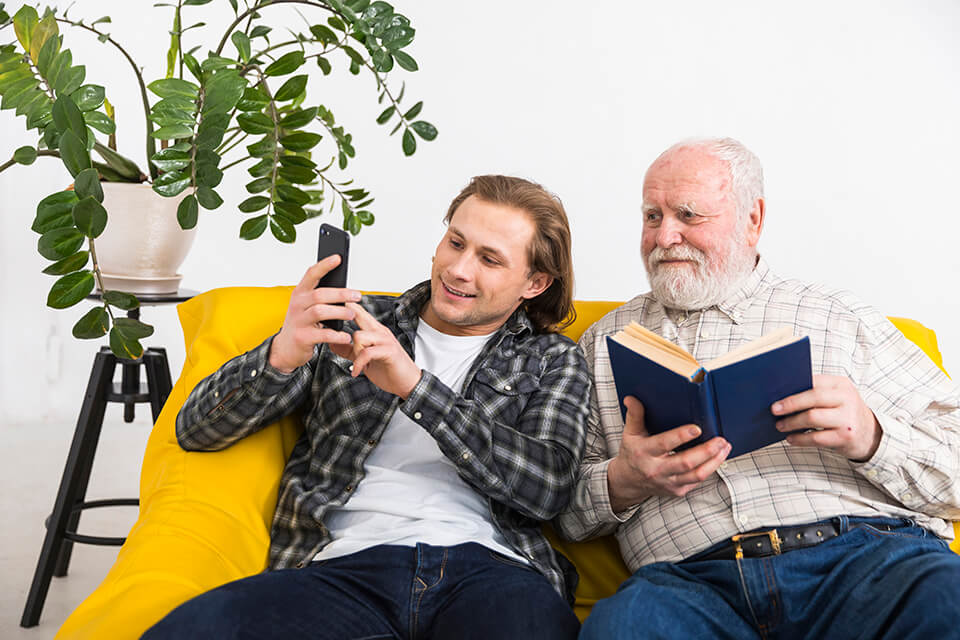 Father and son sitting on the yellow couch, taking a selfie