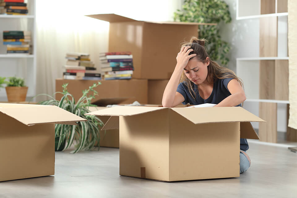 A girl holding her head and leaning on a box