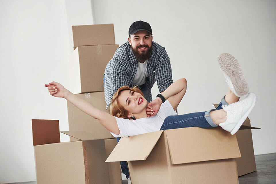 A happy woman sitting in the box, a man behind her