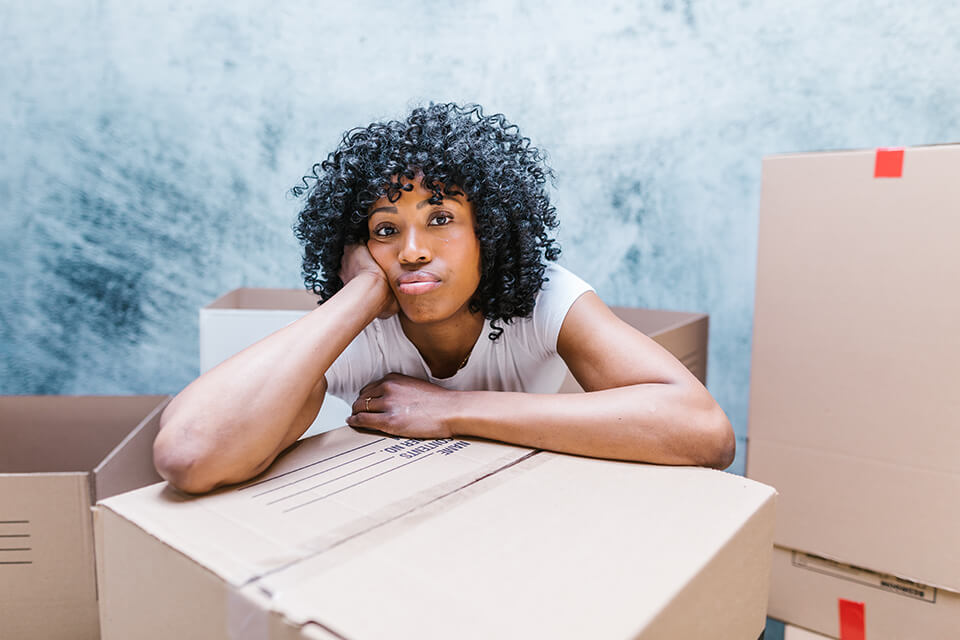 A sad girl leaning on packed boxes