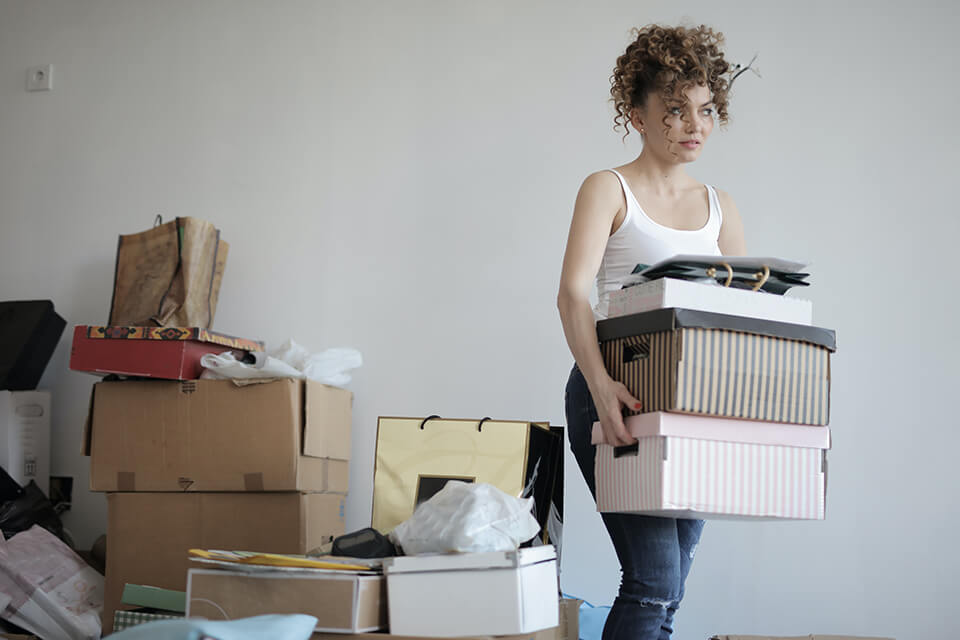 Woman carrying boxes, a pile of boxes behind her