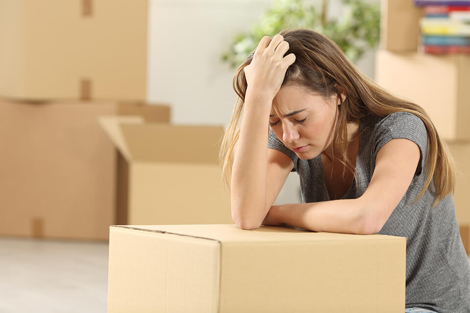A worried woman holding her head and leaning on a box, surrounded by boxes