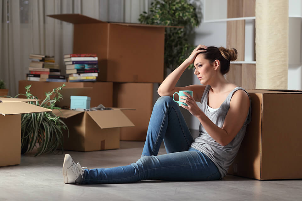 Worried woman sitting on the floor, holding her head and a mug, surrounded by boxes